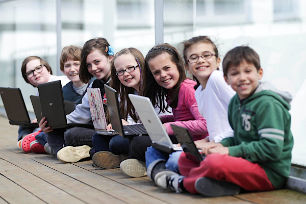 Smiling children with computers on their lap