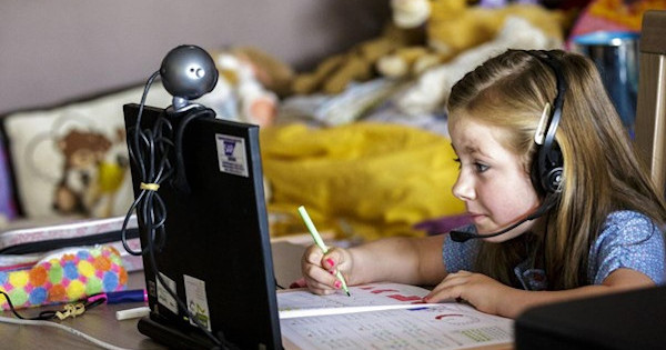 child using a computer and learning at a distance from her bedroom